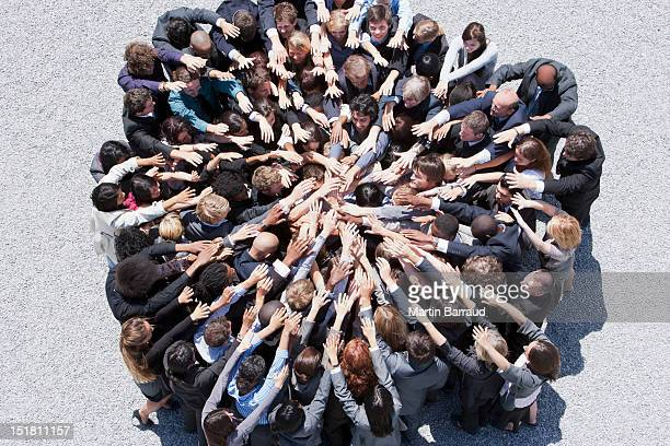 crowd of business people forming huddle with extended arms - dedication stock pictures, royalty-free photos & images