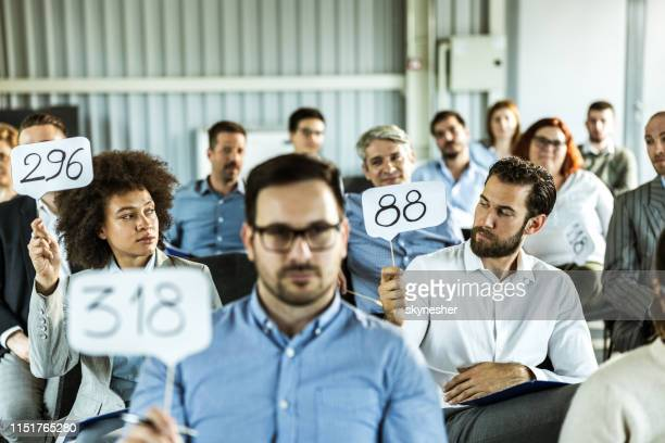crowd of business people having an auction in a board room. - auction stock pictures, royalty-free photos & images