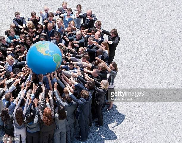 Crowd of business people in huddle reaching for globe
