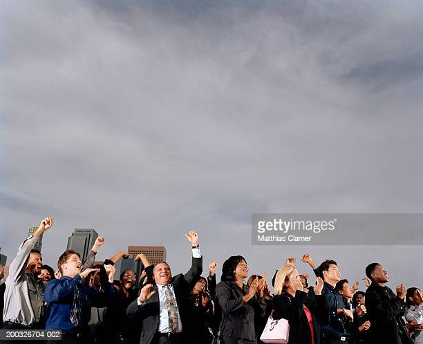 Crowd of businesspeople cheering