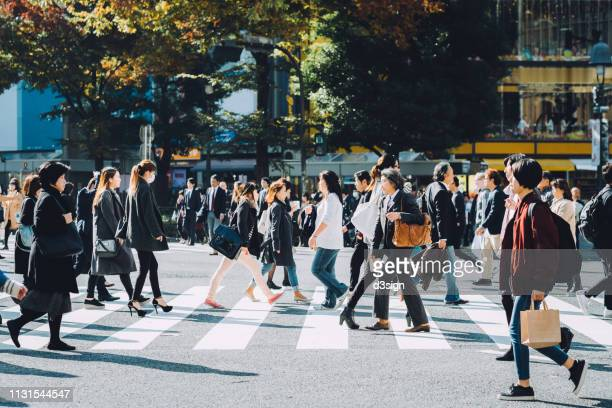 crowd of busy commuters crossing street in shibuya crossroad, tokyo - affollato foto e immagini stock
