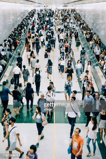 crowd of busy commuters walking through platforms at subway station during office peak hours in the city - 地下鉄のプラットホーム ストックフォトと画像