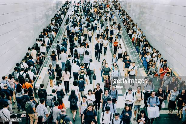 crowd of busy commuters walking through platforms at subway station during office peak hours in the city - atestado fotografías e imágenes de stock