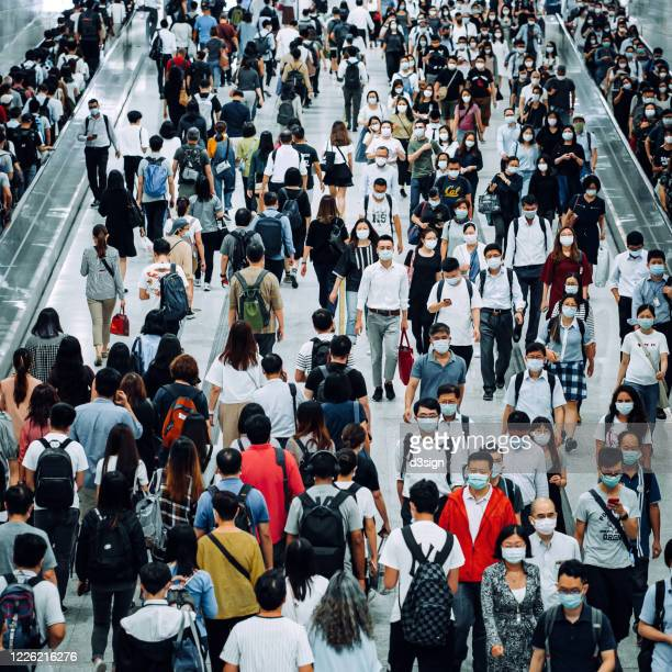 crowd of busy commuters with protective face mask walking through platforms at subway station during office peak hours in the city - 地下鉄のプラットホーム ストックフォトと画像