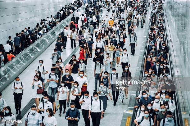 crowd of busy commuters with protective face mask walking through platforms at subway station during office peak hours in the city - china coronavirus stock pictures, royalty-free photos & images