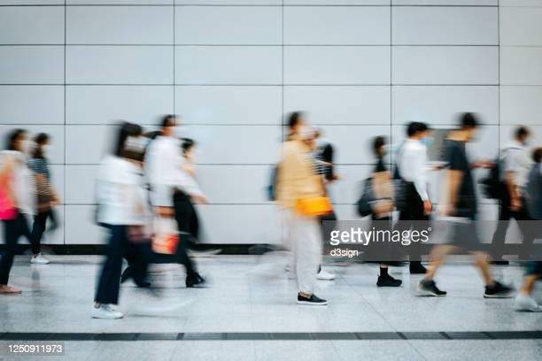 crowd of busy commuters with protective face mask walking through platforms at subway station during office peak hours in the city - station stock pictures, royalty-free photos & images