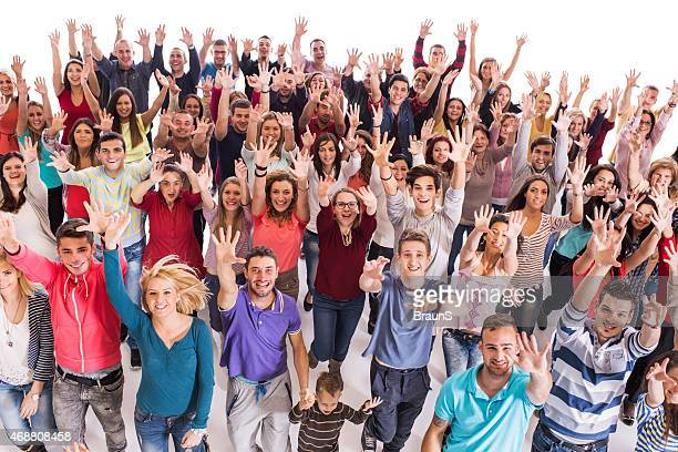 Crowd of cheerful people with raised hands.