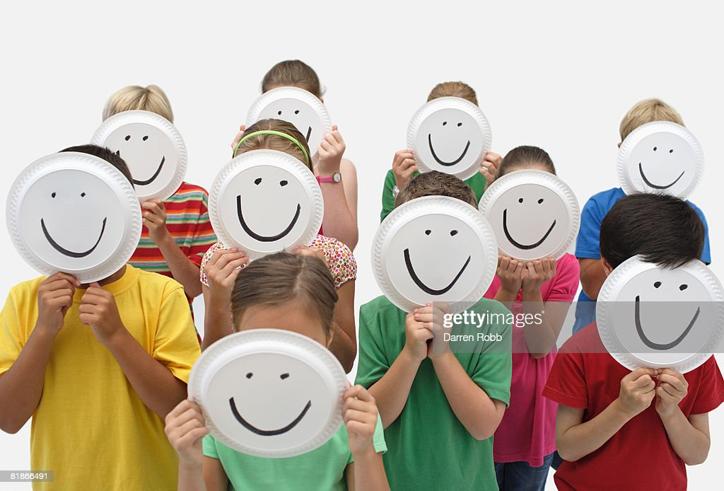 Crowd of children holding paper plates over thier faces with smiley faces on them  Stock & Crowd Of Children Holding Paper Plates Over Thier Faces With Smiley ...
