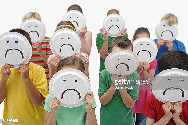crowd of children holding paper plates with unhappy faces on them - jaded pictures stock pictures, royalty-free photos & images