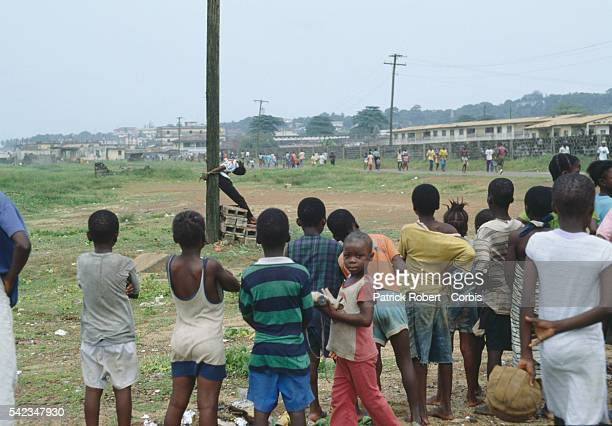 A crowd of children observes the slumped body of a young Armed Forces of Liberia soldier accused of looting and murder who has just been executed by...