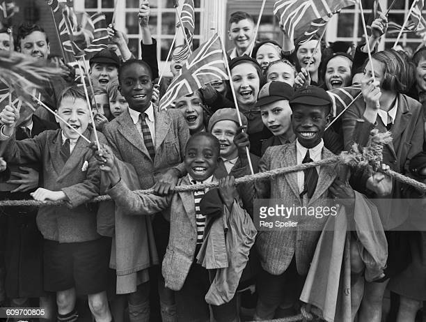 Crowd of children waving union jacks as Queen Mary, wife of King George V, visits Brixton in south London to open the new Lambeth Town Hall, 14th...