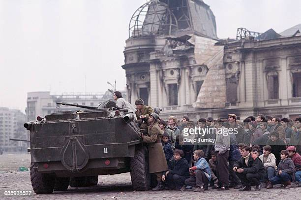 A crowd of civilians hide behind a People's Army tank in Republic Square after the overthrow of Romanian dictator Nicolae Ceausescu