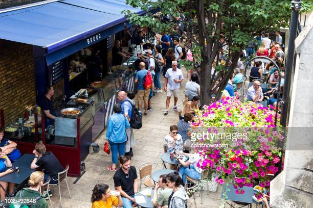 crowd of customers and tourists at food stall in borough market, london, uk - borough market stock pictures, royalty-free photos & images
