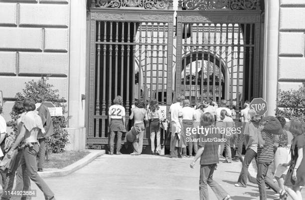 Crowd of demonstrators, from the back, standing in front of a large iron gate during the Kent State/Cambodia Incursion Protest, Washington, District...
