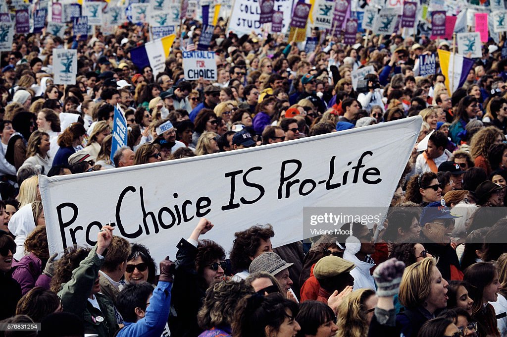 A crowd of demonstrators hold pro-choice signs and banners during an abortion rights march in Washington, DC. The banner reads, 'Pro-Choice IS Pro-Life.'