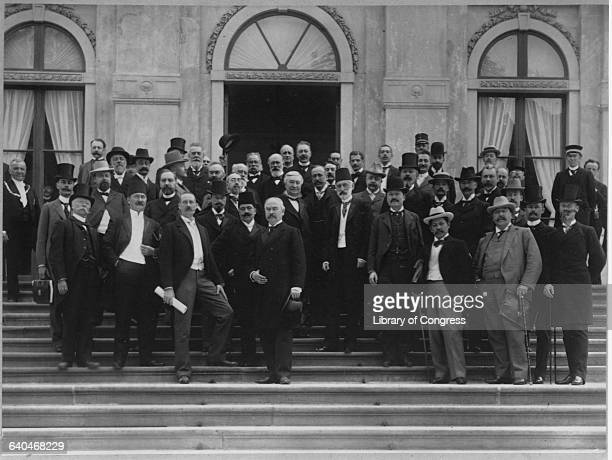 A crowd of diplomats from all over the word stand behind Russian diplomat Fyodor Martens for a first general peace conference in 1899 which Martens...