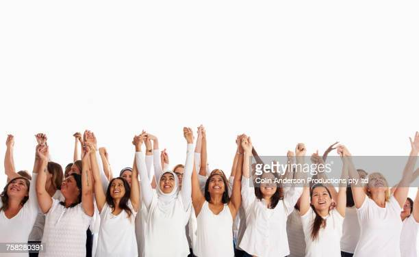 Crowd of diverse women holding hands with arms raised