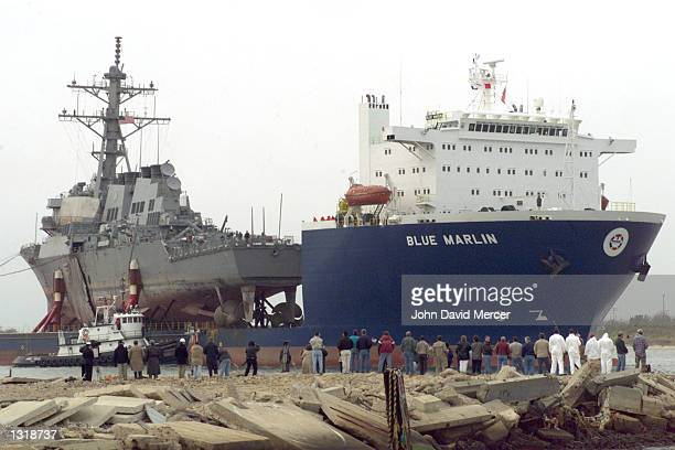 A crowd of dock workers gather as the USS Cole is returned back to the United States December 13 2000 at Ingalls Shipbuilding in Pascagoula MS The...