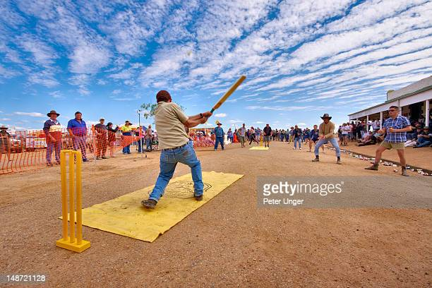 Crowd of drinkers and spectators being entertained with friendly game of cricket in the main street of Birdsville in front of the Birdsville Hotel.