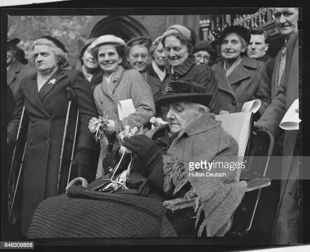 A crowd of elderly people stand around Mrs Matilda Ross in her wheelchair after she has received her traditional Maundy Money