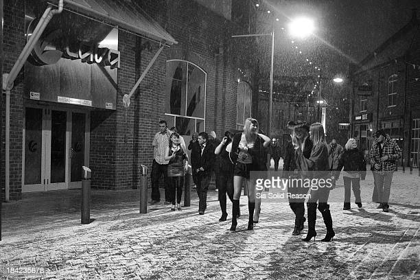 Crowd of english teenagers walks scantily clad / not enough clothes in the snow on the way to another thursday night drinking binge.