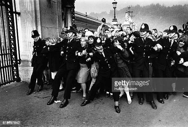 A crowd of excited fans rush against a line of police officers at the gates of Buckingham Palace in hopes of a glimpse of the 1960s rock supergroup...