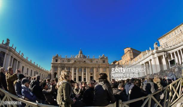 A crowd of faithful and tourists listen to Pope Francis delivering his message from the window of the Apostolic palace overlooking St Peter's square...