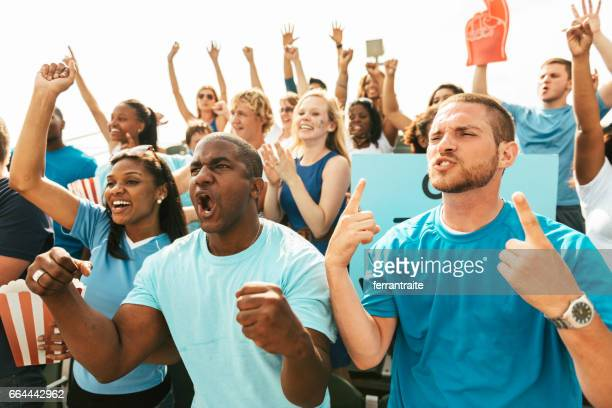 crowd of fans cheering from stadium bleachers - supporter stock pictures, royalty-free photos & images