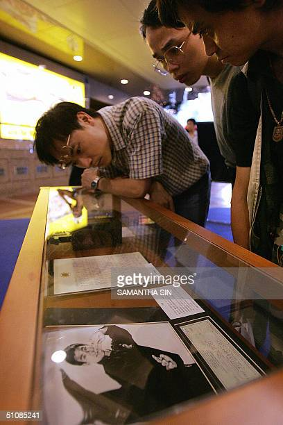 A crowd of fans look at Bruce Lee's personal stuff of his handwritten letter a signed cheque and some of his trophies during a mini exhibition on a...