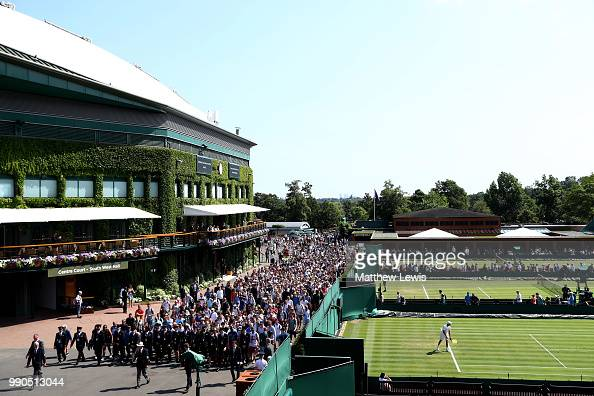 A crowd of fans wait to enter the courts on day two of the Wimbledon Lawn Tennis Championships at All England Lawn Tennis and Croquet Club on July 3...