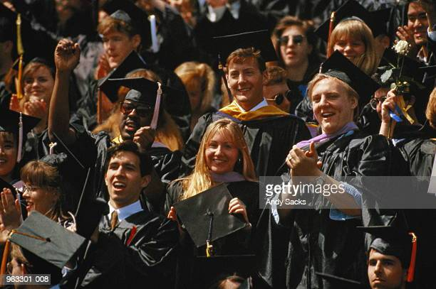 crowd of graduates wearing graduation caps and growns - graduation crowd stock pictures, royalty-free photos & images