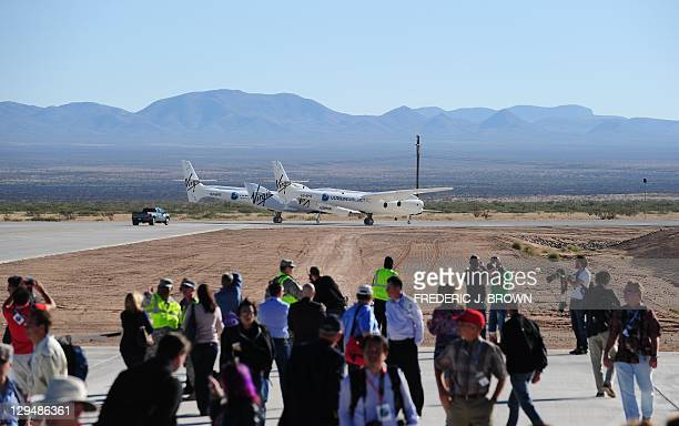 Crowd of guests and media gather for a view of WhiteKnightTwo, carrying SpaceShipTwo, about to take flight over Spaceport America, northeast of Truth...