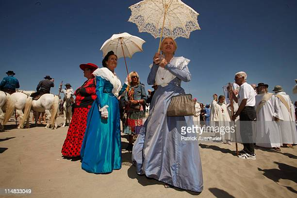 A crowd of gypsies and nongypsy pilgrims gaurdians on horseback and Arlesienne girls in costume accompany the 'craft' with the statues of Two Marys...