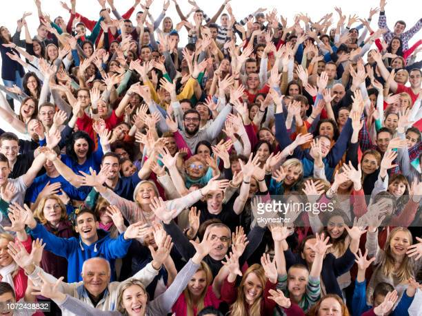 menigte van gelukkige mensen met uitgestrekte armen camera kijken. - grote groep mensen stockfoto's en -beelden
