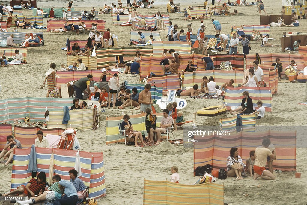 A crowd of holidaymakers use windbreaks to make the most of a British holiday on the beach at Perranporth, Cornwall circa 1970.