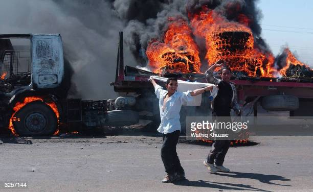 A crowd of Iraqis loyal to radical Shia cleric Moqtada alSadr cheer after attacking and burning two vehicles in a convoy of auto parts and fuel...