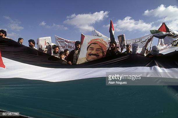A crowd of Jordanians hold a giant flag and a picture of Saddam Hussein at a demonstration in Amman Jordan The demonstrators were showing their...
