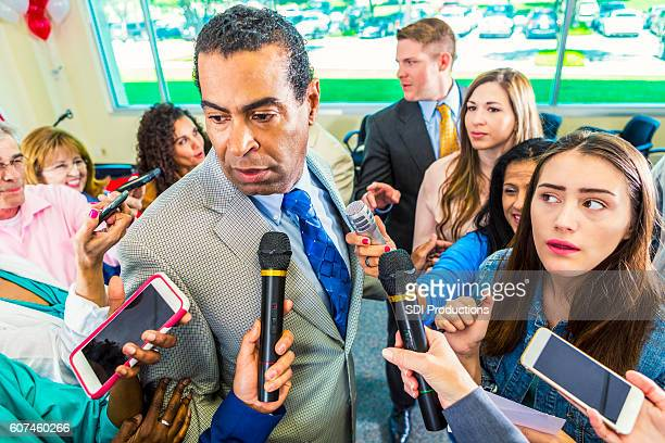 A crowd of journalists surround political candidate