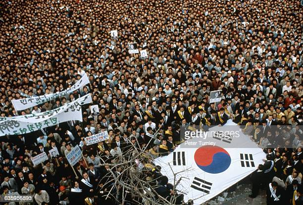 A crowd of Koreans holds signs and a South Korean flag at the 1988 Summer Olympics