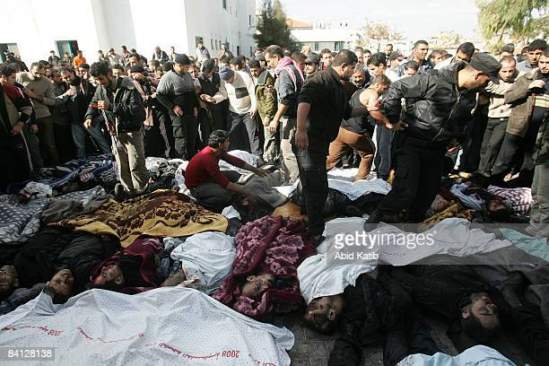 A crowd of men gather around bodies of Palestinians laid out on the ground outside Shifa hospital on December 27 2008 in Gaza City Gaza Israel's air...