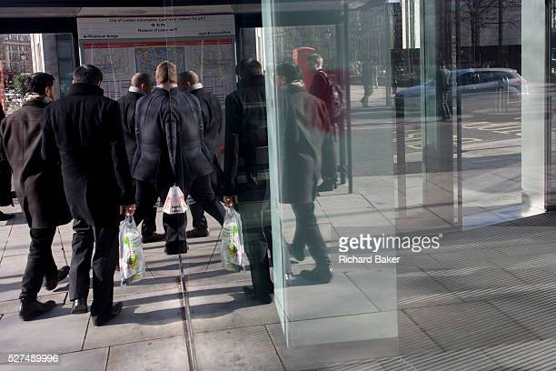 A crowd of men on their lunch break seemingly pass through their own reflections in a humerous scene in plate glass of a pedestrian walking through a...