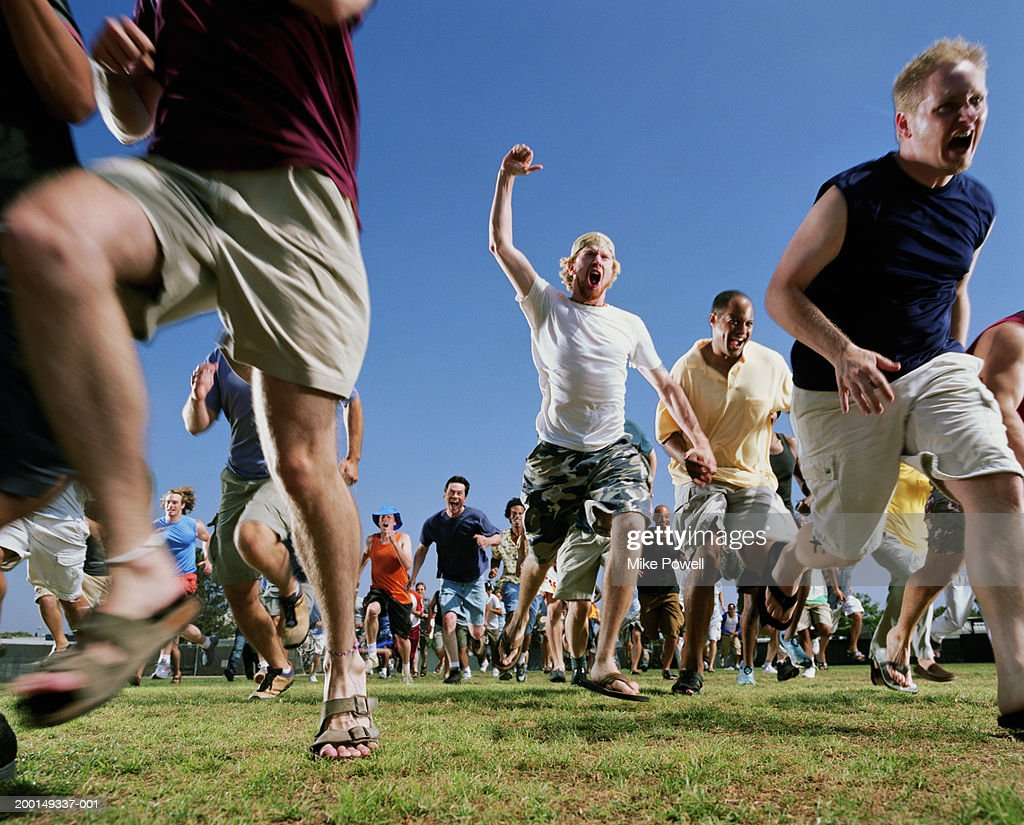 Crowd of men running, low angle : Stock Photo
