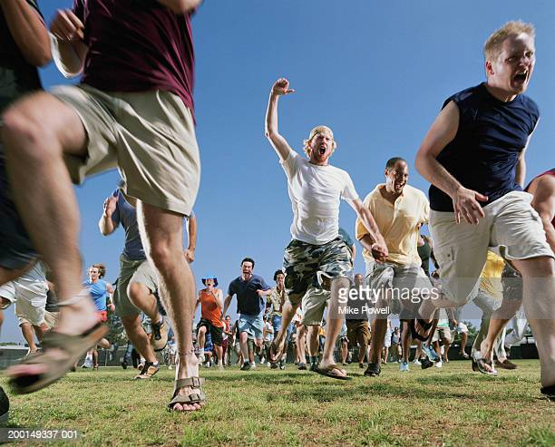 Crowd of men running, low angle
