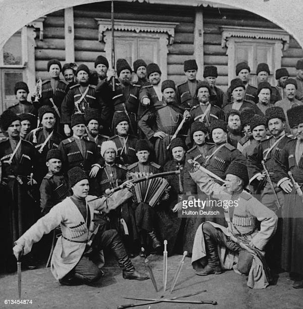 A crowd of men watch two of their colleagues perform a cossack dance using swords