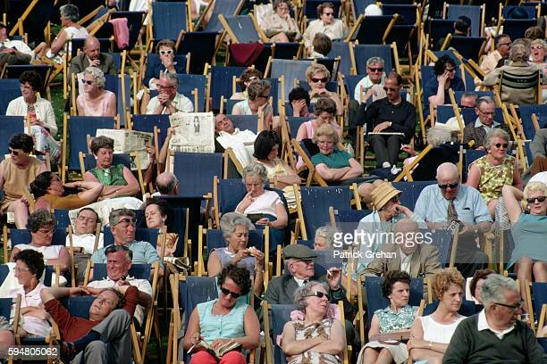 A crowd of mostly elderly people lounge in folding chairs at a Liverpool park in summer