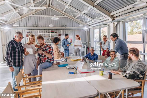 crowd of multi-tasking freelancers working in a modern office. - human age stock photos and pictures
