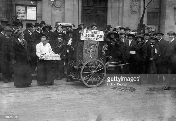 A crowd of onlookers watch Suffragettes advertise their 'Self Denial Week' on London's Kingsway March 3 1913 | Location Kingsway London England UK