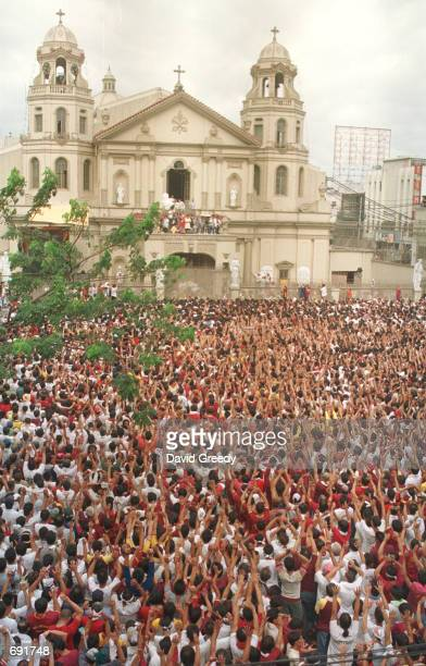 A crowd of over 200000 devotees await the procession of the Black Nazarene outside Quiapo Church January 9 2002 in the center of Manila Philippines...