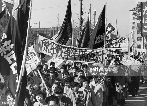 A crowd of over 6000 demostrators marches through Hibiya park carrying signs and banners to protest the placement of a nuclear weapons test base in...