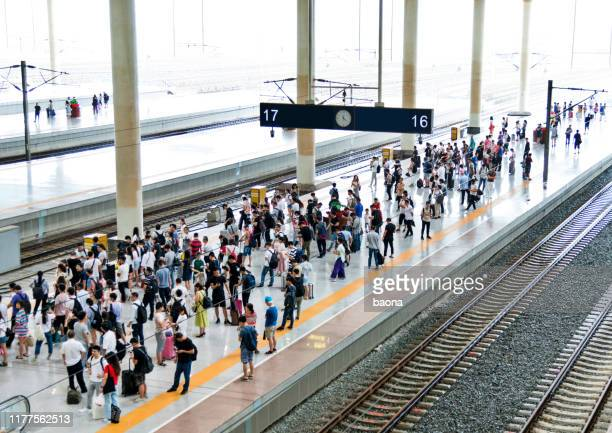 crowd of passengers waiting on station platform - railway station stock pictures, royalty-free photos & images